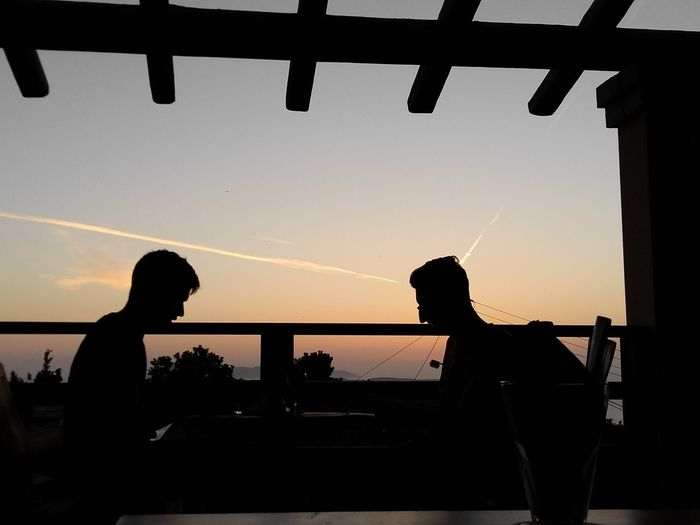 Silhouette people sitting by railing against sky during sunset