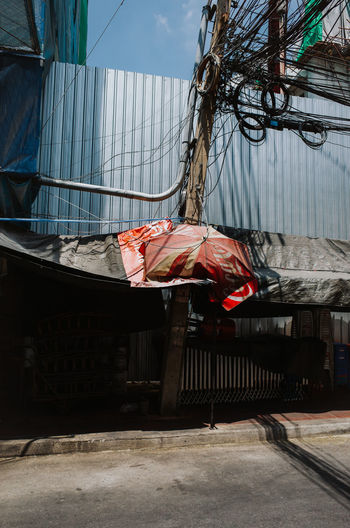 Empty street with Coca-Cola umbrella in Bangkok, Thailand Architecture Built Structure Day Building Exterior No People City Nature Sunlight Outdoors Building Abandoned Bed Garbage Red Relaxation Railing Textile Plastic Pillow Electricity  Electricity Pylon Thailand Bangkok ASIA