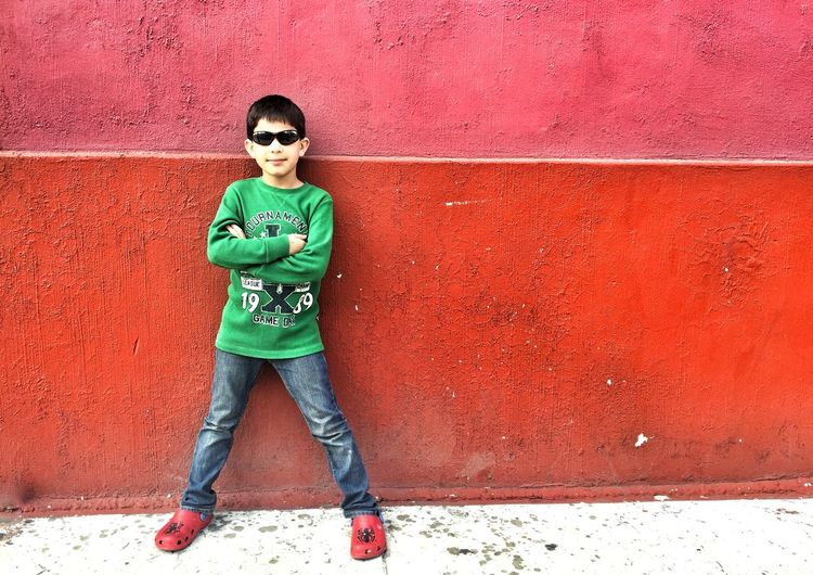 Portrait of boy with arms crossed standing against red wall