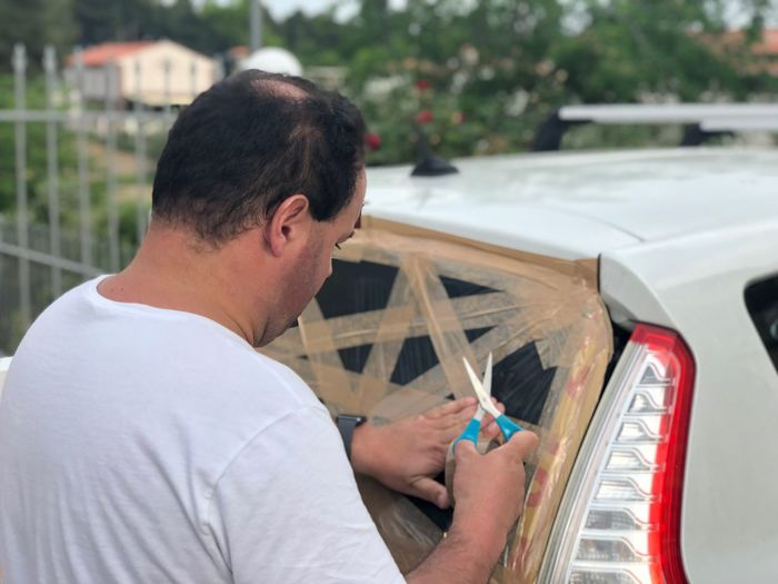 Man Fixing Broken Rear Windshield Of Car With Tape