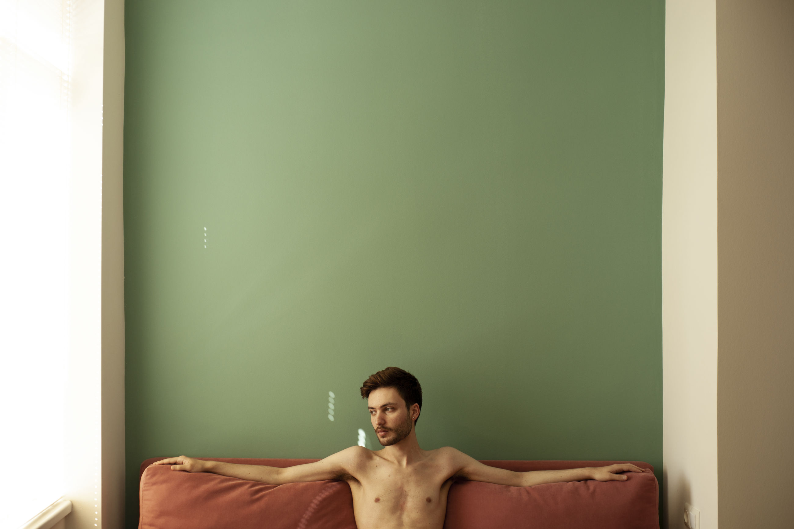 one person, young adult, indoors, shirtless, front view, real people, portrait, young men, lifestyles, domestic room, furniture, looking at camera, sitting, men, adult, copy space, leisure activity, relaxation, wall - building feature
