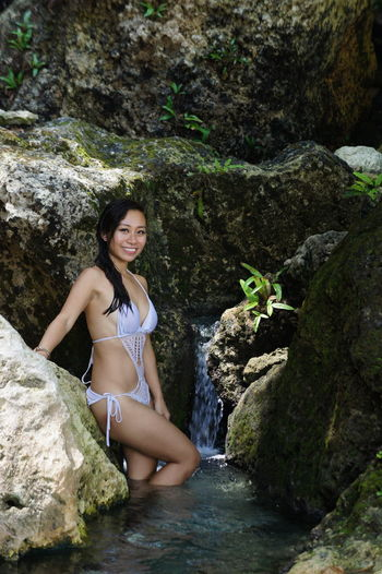Portrait of happy young woman in bikini on rock formation