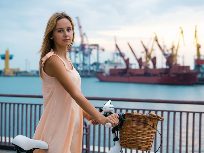 Portrait of beautiful woman with bicycle at harbor