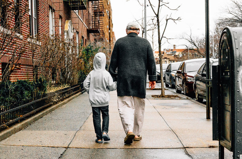 Full Length Of Grandfather With Grandson Walking On Sidewalk