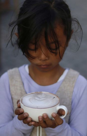 Close-up of girl holding coffee cup