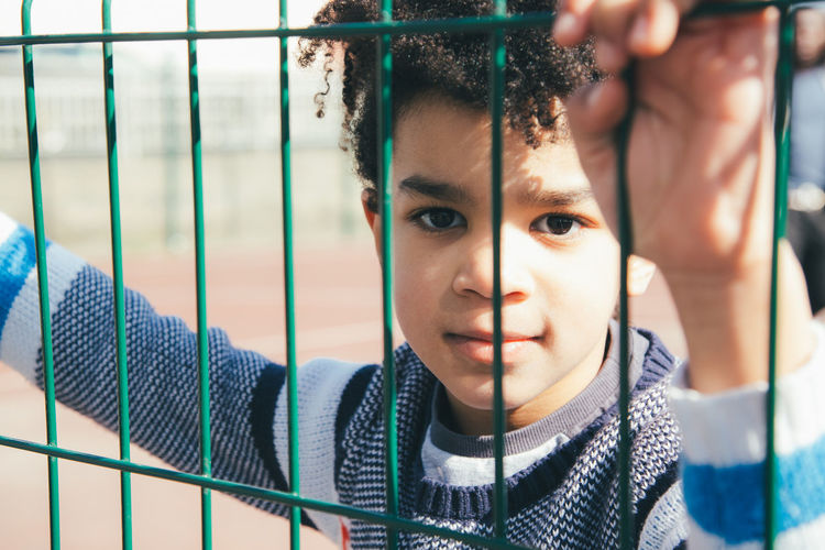 Portrait of cute boy seen through fence