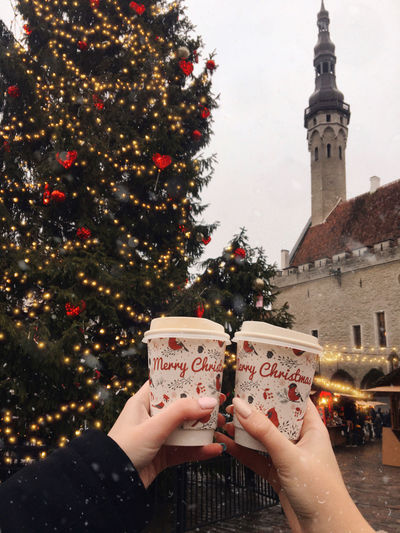Cropped hands of woman holding disposable cups against christmas tree