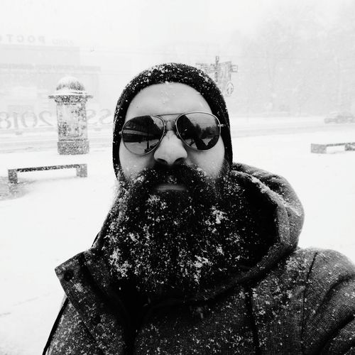 Portrait of man wearing sunglasses during snowfall in city
