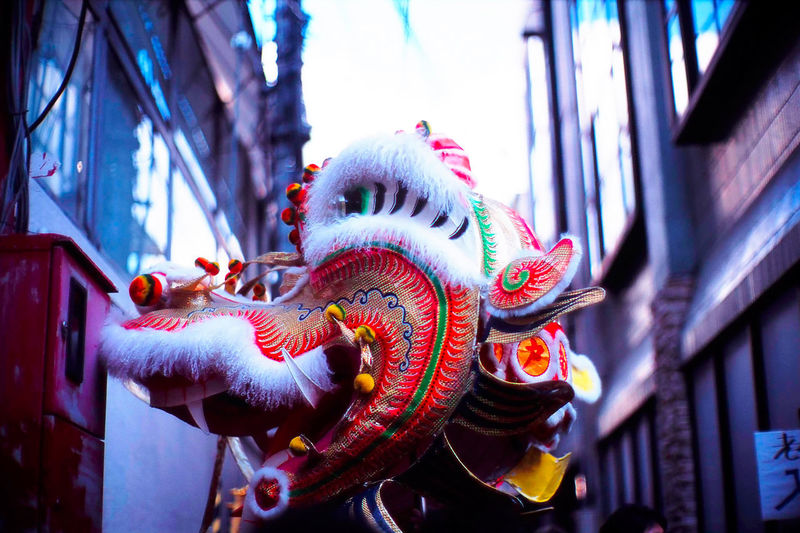 Chinese dragon amidst buildings in city at lunar new year