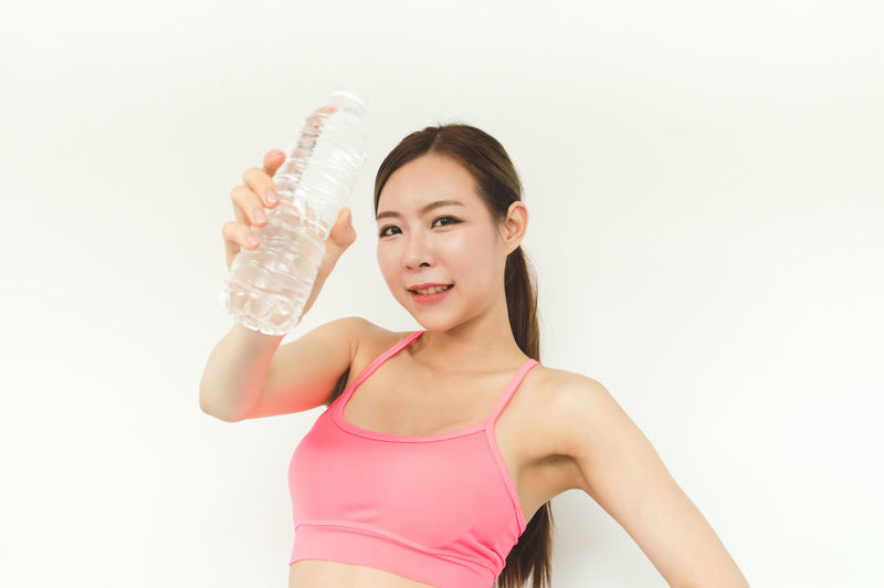 Adult Beautiful Woman Bottle Clothing Front View Hand Healthy Lifestyle Holding Indoors  Lifestyles Looking At Camera One Person Portrait Smiling Sport Standing Studio Shot Waist Up Water White Background Women Young Adult Young Women