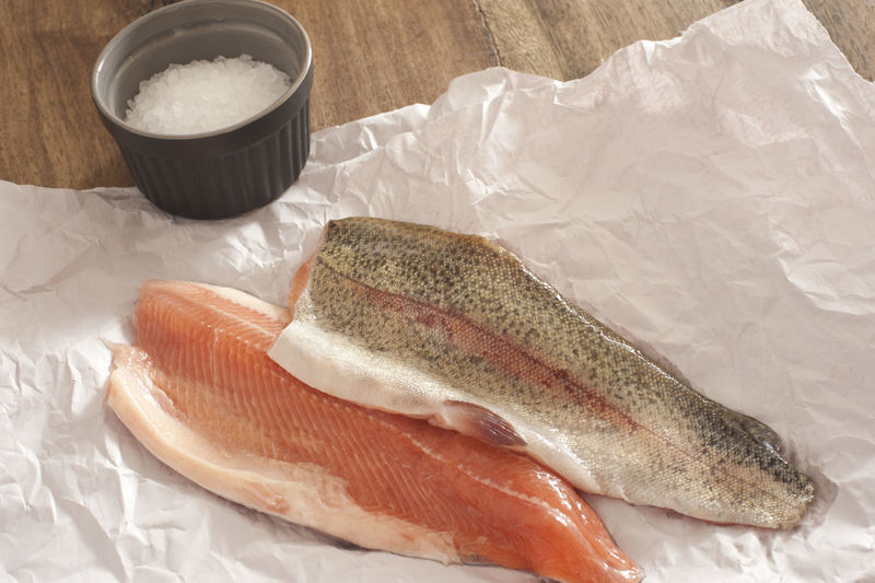 High angle view of salmon with salt on paper at table