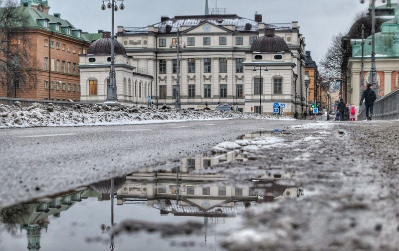 Reflection of buildings in puddle on street in winter