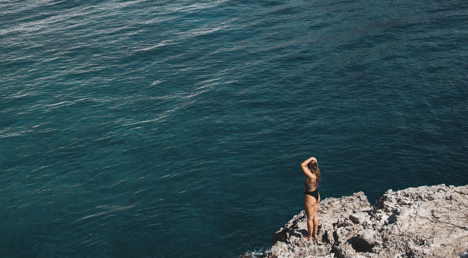 High angle view of woman standing on rock at sea