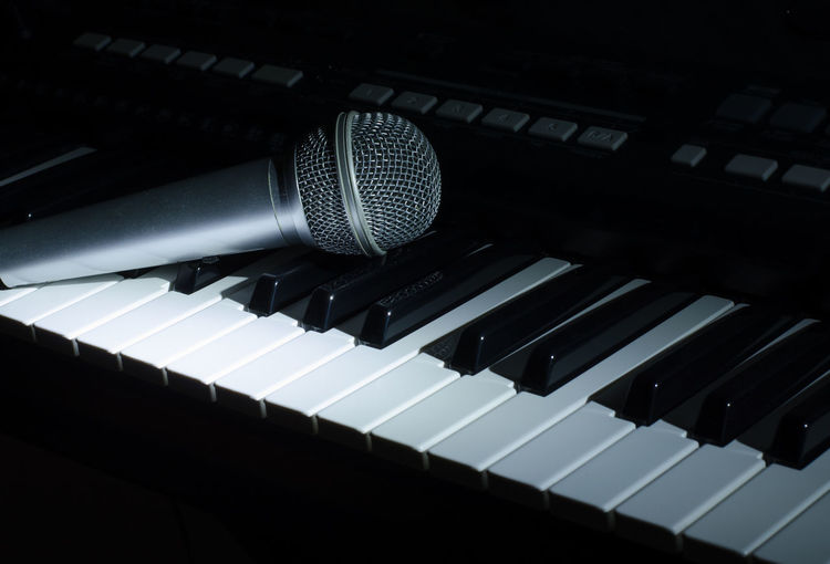 Close-up of microphone on piano keys