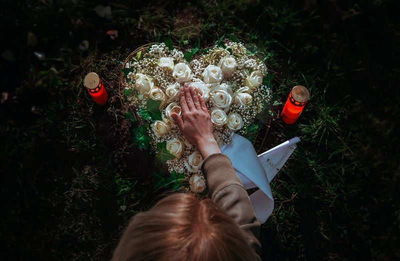 High angle view of woman touching heart shape flower at cemetery