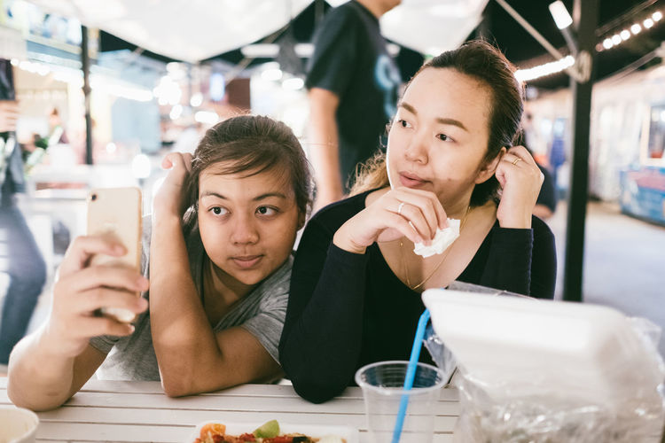 Woman Taking Selfie With Friend In Restaurant