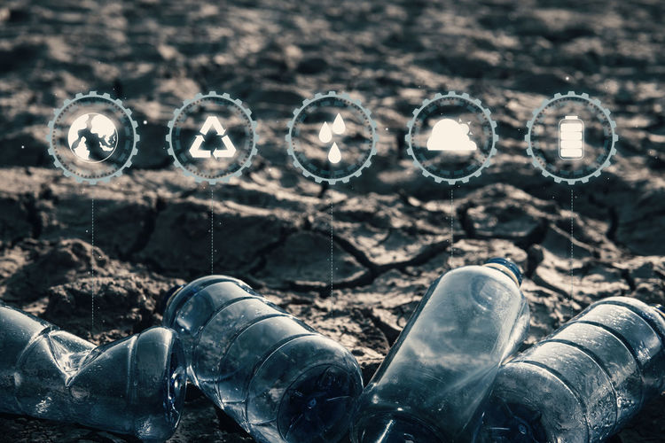 Close up bottle plastic with icon on crack ground beside the lake outdoor on the baking hot day, Drought and environmental problems. Close-up Nature Outdoors Day Hot Drought Environment Problem Protection Garbage Bottle Icon Container Pollution