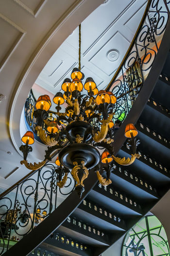 Architecture interior, candelabra and curved staircase viewed from below. Building interior detail, spiral staircase, ceiling and chandelier. Light Railing Rich Architecture Background Below Black Building Candelabra Ceiling Chandelier Curved  Decoration Design Detail Indoors  Interior Luxury Noble Old Pattern Spiral Staircase Viewed Vintage