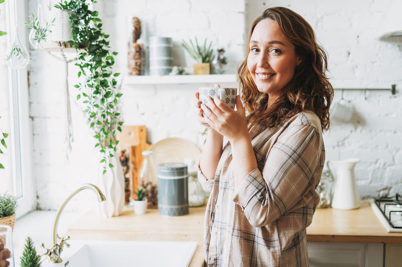 Portrait of smiling woman holding coffee cup standing at home