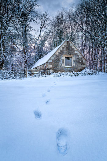Footprints leading to a stone barn in heavy snow Snow Cold Temperature Winter Built Structure Tree Building Exterior Architecture Bare Tree Nature Building No People House Landscape Day Plant Beauty In Nature Scenics - Nature White Color Land Outdoors Footprints In The Snow FootPrint