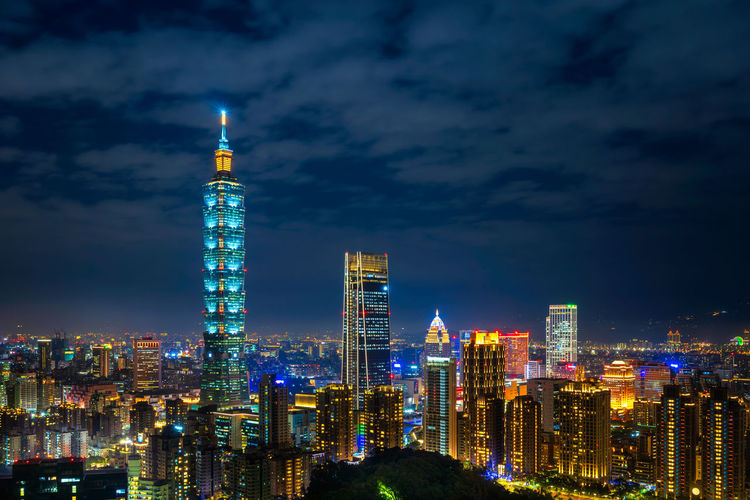 Illuminated buildings in city against sky at night. taipei.