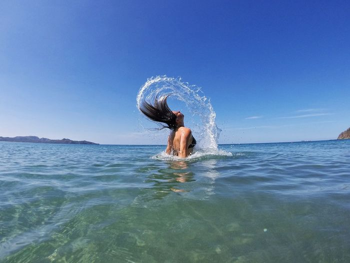 Woman Tossing Hair In Sea Against Clear Sky