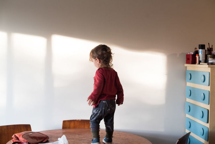Full length of boy standing on table at home