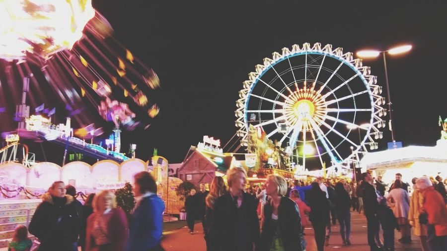 People at amusement park against sky at night