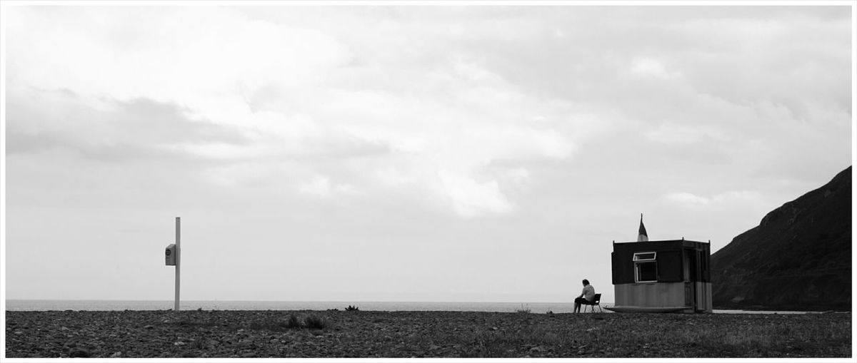 Person sitting on chair by sea against sky at bray
