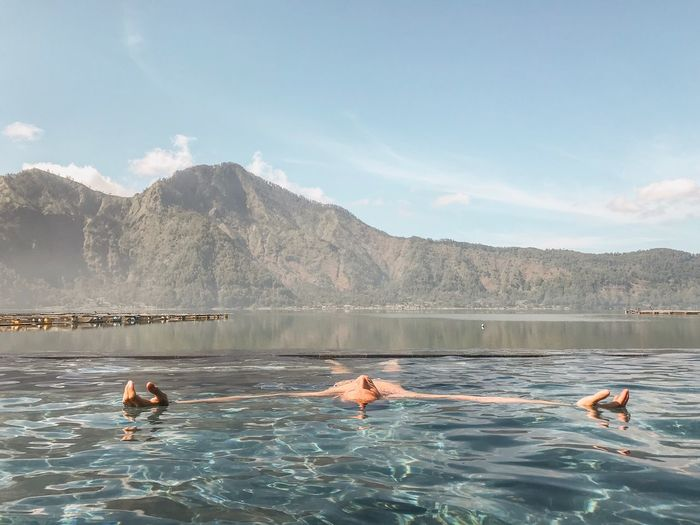 Man Swimming In Infinity Pool By Lake Against Sky