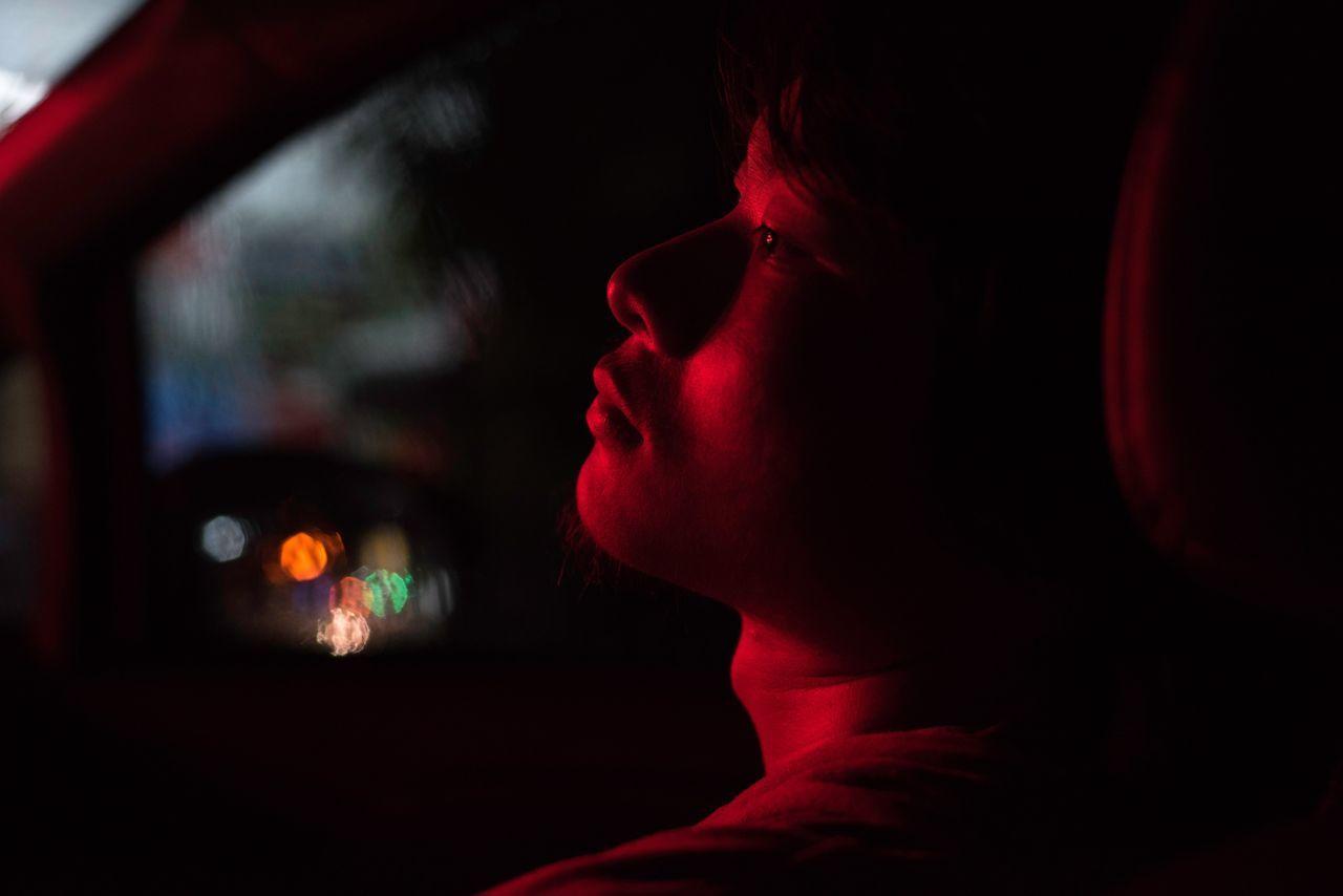 Light falling on thoughtful man sitting in car