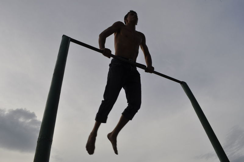 Low angle view of shirtless man exercising against sky