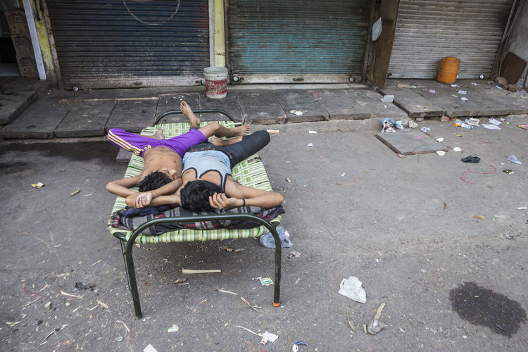two person sleep in bed in front of shop in Chandni Chow, Old Delhi Candid Candid Photography Casual Clothing City Life Day Indian Indianstories Indiapictures Leisure Activity Life Lifestyles Live Morninglife Outdoors Sleep Snapshot Street Photography Streetlife