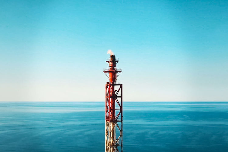 Tower by sea against clear blue sky