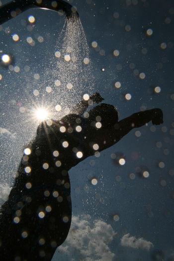 Low Angle View Of Silhouette Woman Taking Shower Against Sky