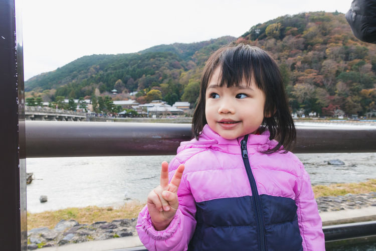 Arashiyama Casual Clothing Childhood Day Front View Leisure Activity Lifestyles Looking At Camera Medium-length Hair Mountain Nature One Person Outdoors Portrait Real People River Sky Smiling Standing Tree Water Young Adult