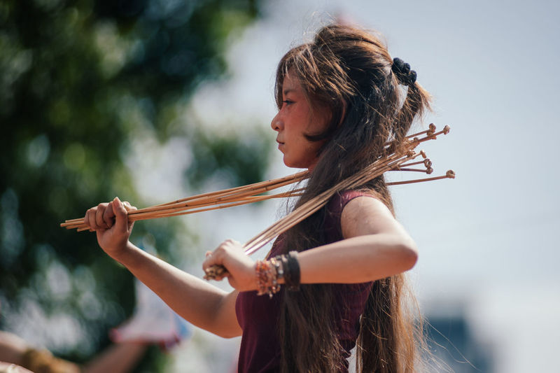Side view of young woman with sticks standing against sky
