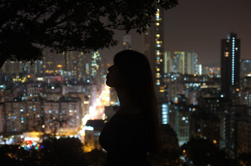 Woman standing against illuminated city at night