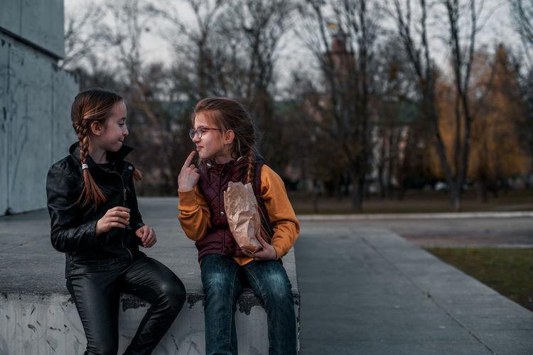Girls talking while sitting at park