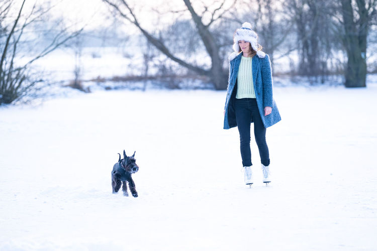 Full length of person with dog on snow covered trees