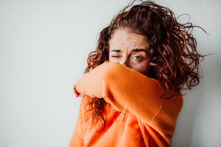 Portrait of woman covering face with hand against wall