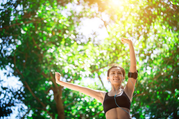 Low Angle View Of Sporty Young Woman Standing With Arms Raised Outdoors