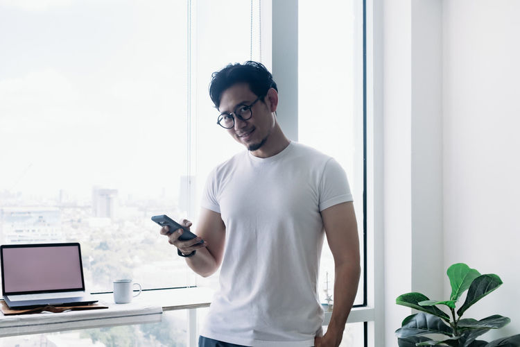 Young man using mobile phone while standing on table