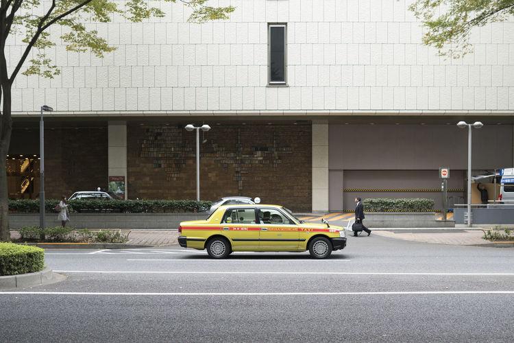 Car on street against buildings in city