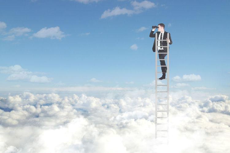 Digital composite image of businessman standing on ladder in cloudscape