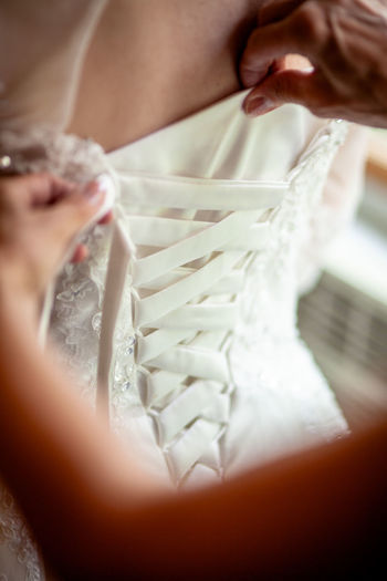 Cropped Hands Of Woman Dressing Bride During Wedding Ceremony