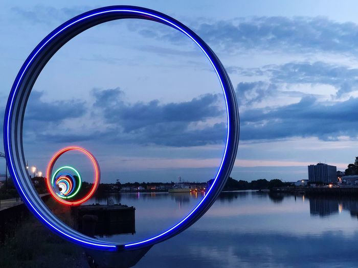 Illuminated rings by river in city against sky during sunset