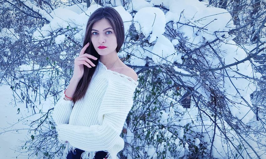 Portrait of young woman standing against snow covered plants