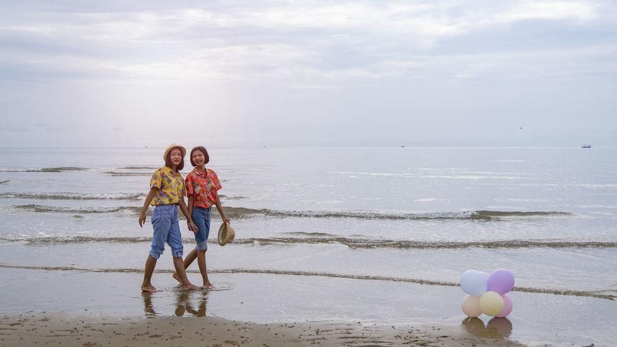 Two young girl walking at the sea at the morning at pranburi.