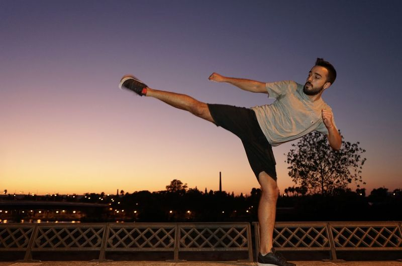 Full length of young man jumping against sky during sunset